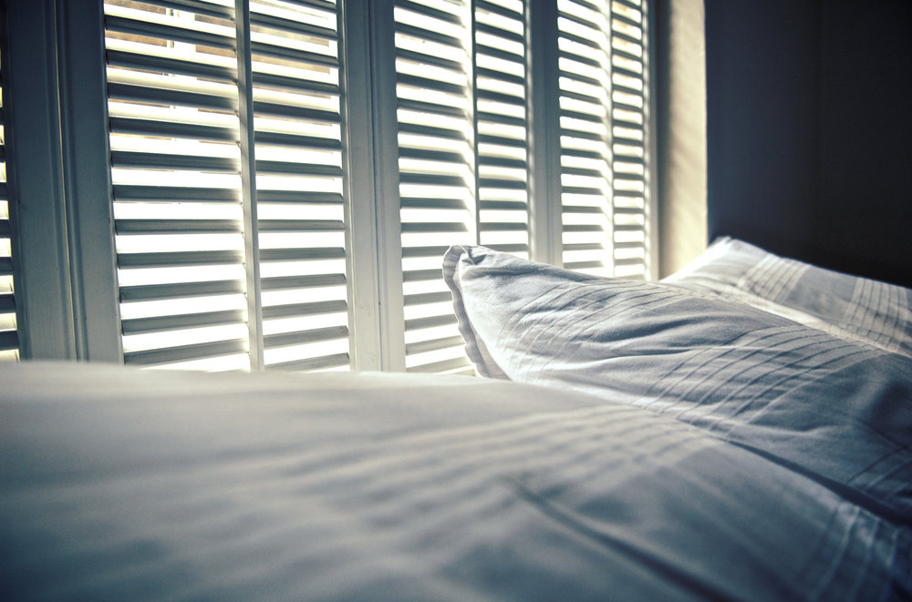 White linen against white shutters with white light behind